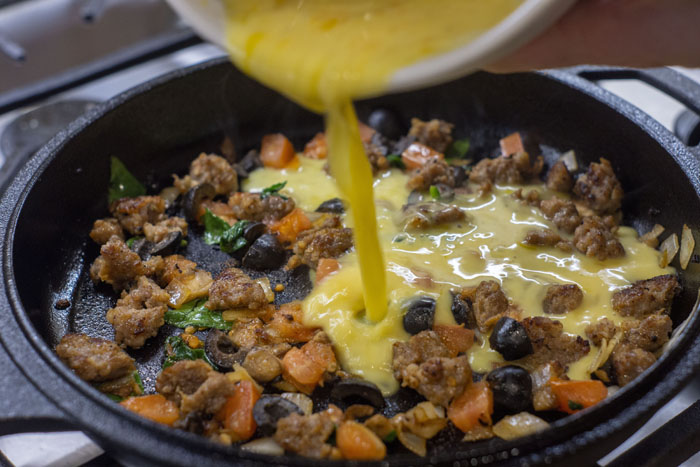 Sausage and vegetables in a cast iron pan with egg pouring into it
