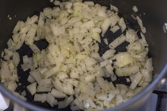 Close up of onions sauteing in a large pot