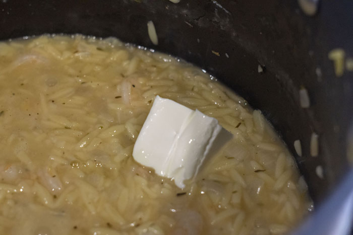 Close up of orzo cooking in a large pot with a piece of cream cheese