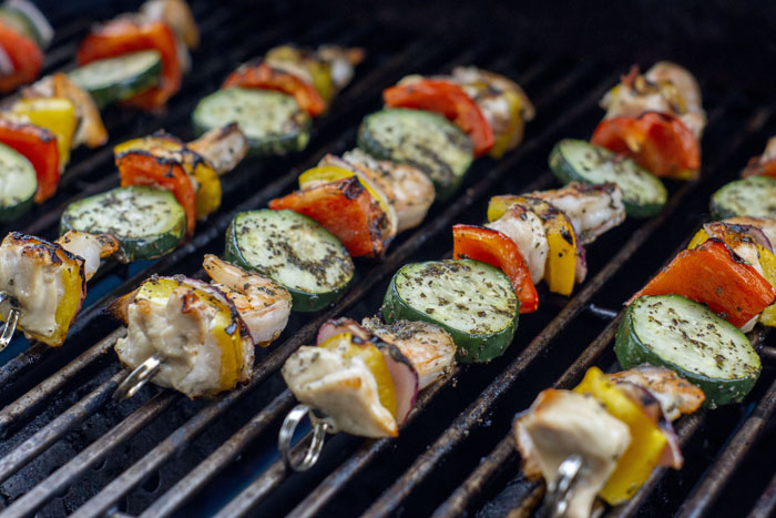 Summer Basil Chicken and Shrimp Kabobs on metal skewers cooking on a grill