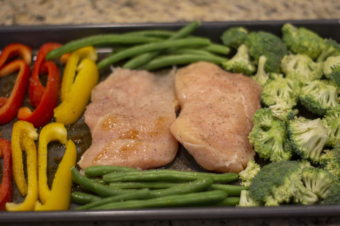 Raw chicken in the middle of a metal sheet pan surrounded by chopped broccoli, green beans, and sliced peppers covered with pepper and seasonings