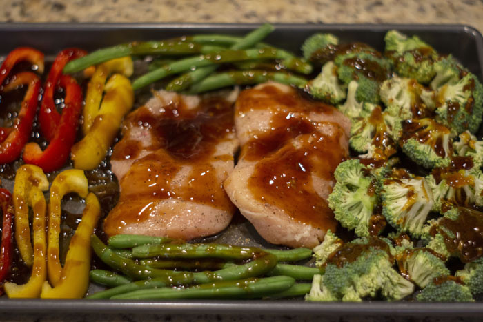 Raw chicken in the middle of a metal sheet pan surrounded by chopped broccoli, green beans, and sliced peppers covered with teriyaki sauce