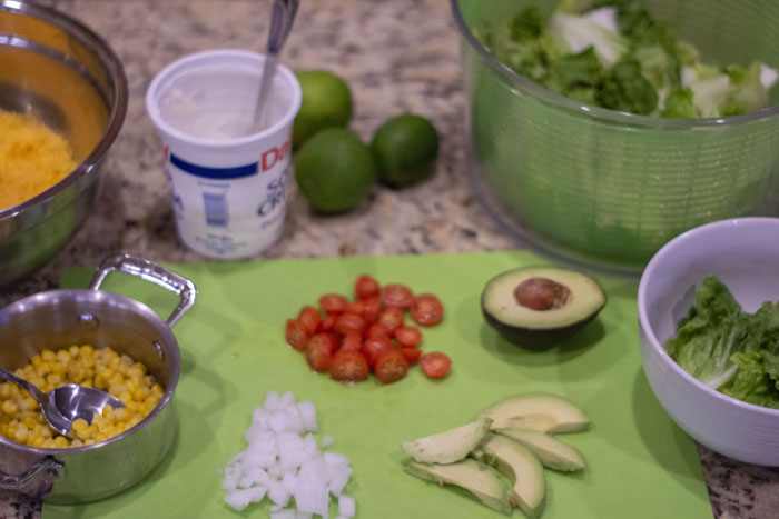 Wide shot of tex-mex bowl ingredients ready to use: cooked corn, shredded cheese, sour cream, limes, tomatoes, diced onion, sliced avocado, lettuce