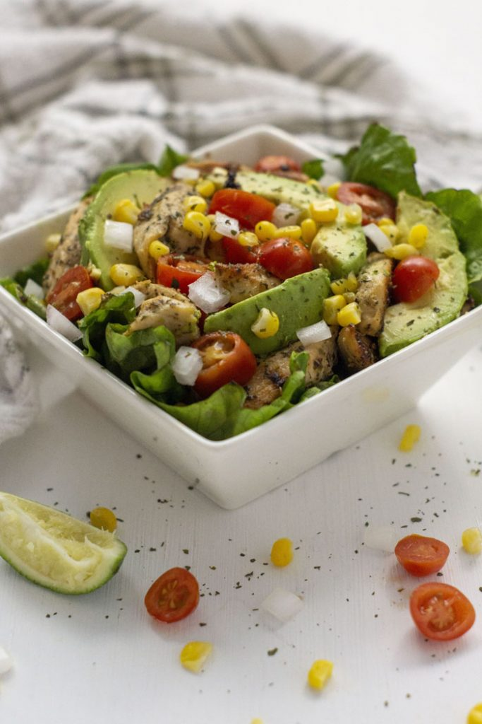 Easy Tex-Mex Bowl in a square white bowl with ingredients around the bowl and a towel in the background (vertical)
