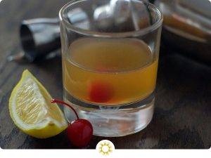 Whiskey Sour cocktail drink in a small glass next to a cherry and slices of lemon on a dark wood surface