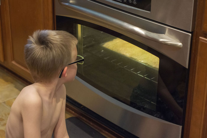 Young boy sitting in front of the oven with the light on watching the breadsticks bake