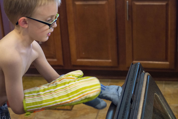 Young boy with two oven mitts opening the oven