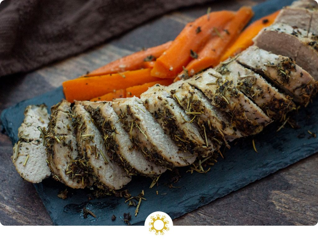 Sliced Italian-Herb Crusted Pork Tenderloin on a slate board with carrots all on a wooden background (with logo overlay)