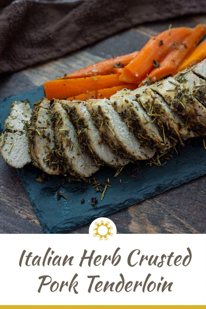 Sliced Italian-Herb Crusted Pork Tenderloin on a slate board with carrots all on a wooden background (with title overlay)
