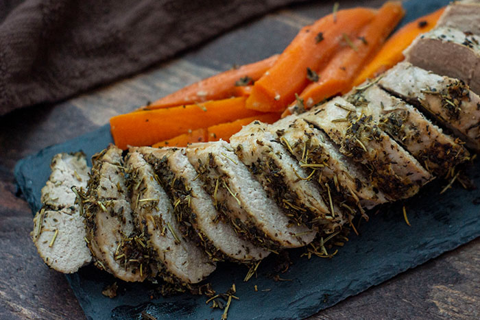 Sliced Italian-Herb Crusted Pork Tenderloin on a slate board with carrots all on a wooden background