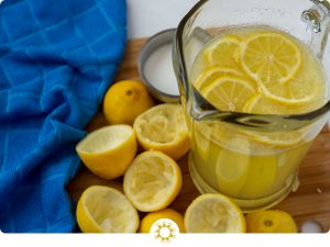 Lemonade in a glass pitcher next to juiced lemons on a wooden board with a blue towel to the side (with logo overlay)