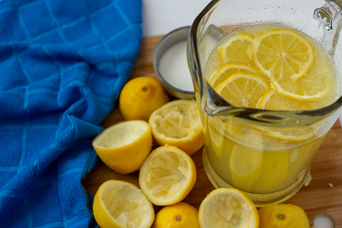 Lemonade in a glass pitcher next to juiced lemons on a wooden board with a blue towel to the side