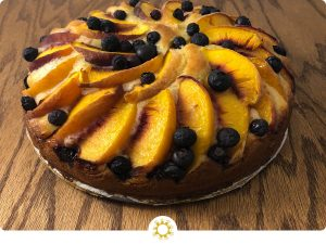 Peach and Blueberry Cake on a wooden surface (with logo overlay)