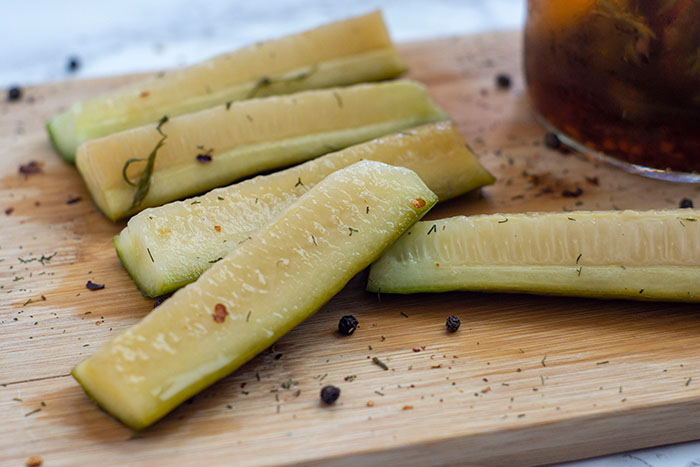 Vertically sliced dill pickles on a wooden cutting board next to a jar of pickles