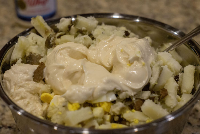 Cooked potatoes, chopped hard-boiled eggs, and miracle whip in a stainless steel mixing bowl