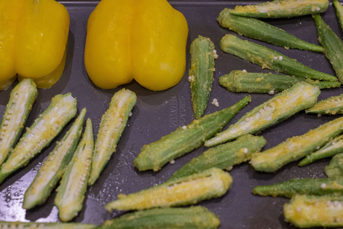 Yellow bell pepper and okra on a metal baking sheet