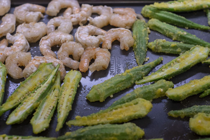 Shrimp and okra on a metal baking sheet