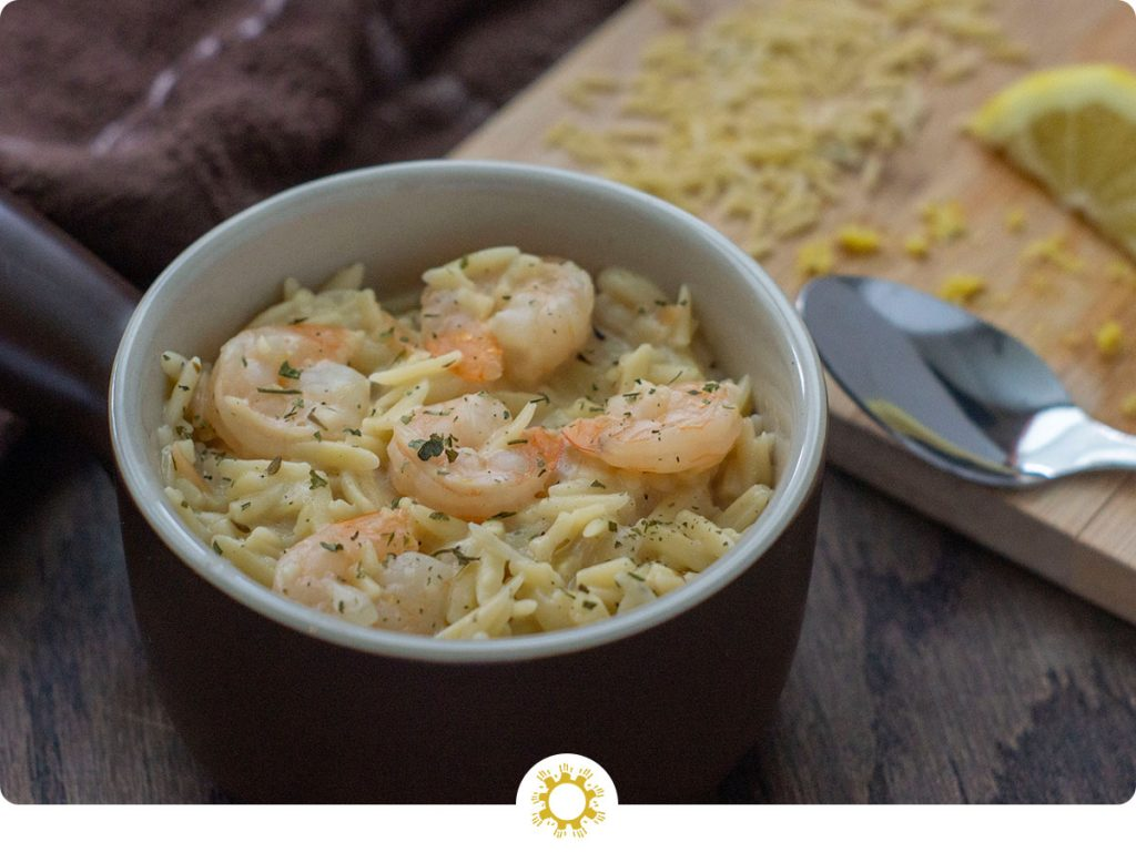Shrimp Orzo with Lemon in a brown and white dish with a wooden board covered with orzo noodles and lemon zest next to a spoon all on a wooden surface (with logo overlay)