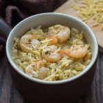Shrimp Orzo with Lemon in a brown and white dish with a wooden board covered with orzo noodles all on a wooden surface (with title overlay)
