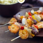 Steak and Shrimp Kabobs on metal skewers on a round brown plate with a brown side bowl and towel behind all on a wooden surface (with title overlay)