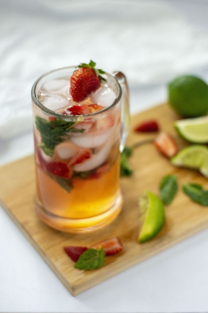 Strawberry mojito in a class on a bamboo cutting board (vertical)