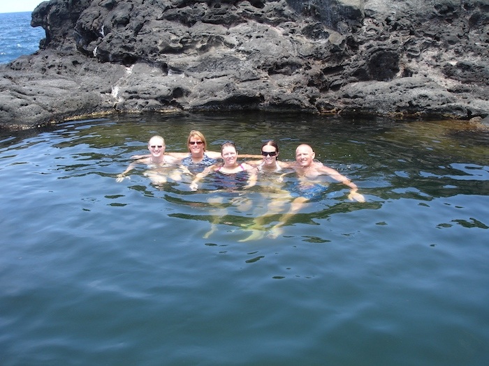 Family in the waters of Hawaii with rocks in the background