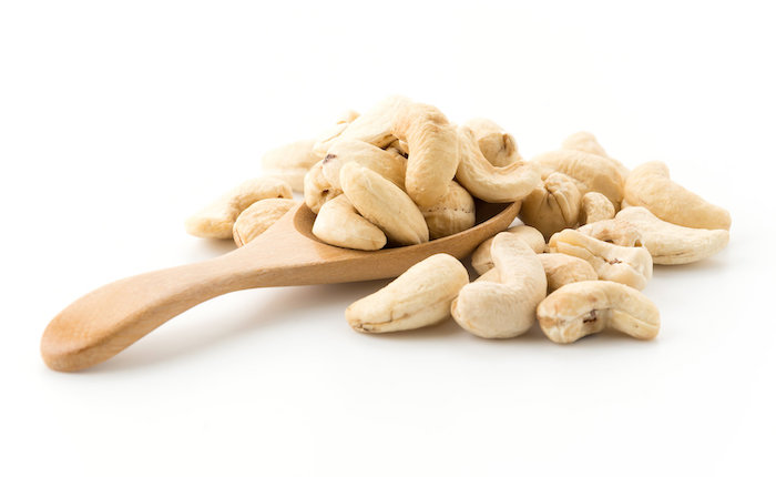 Cashew nuts on a wooden spoon with a white background