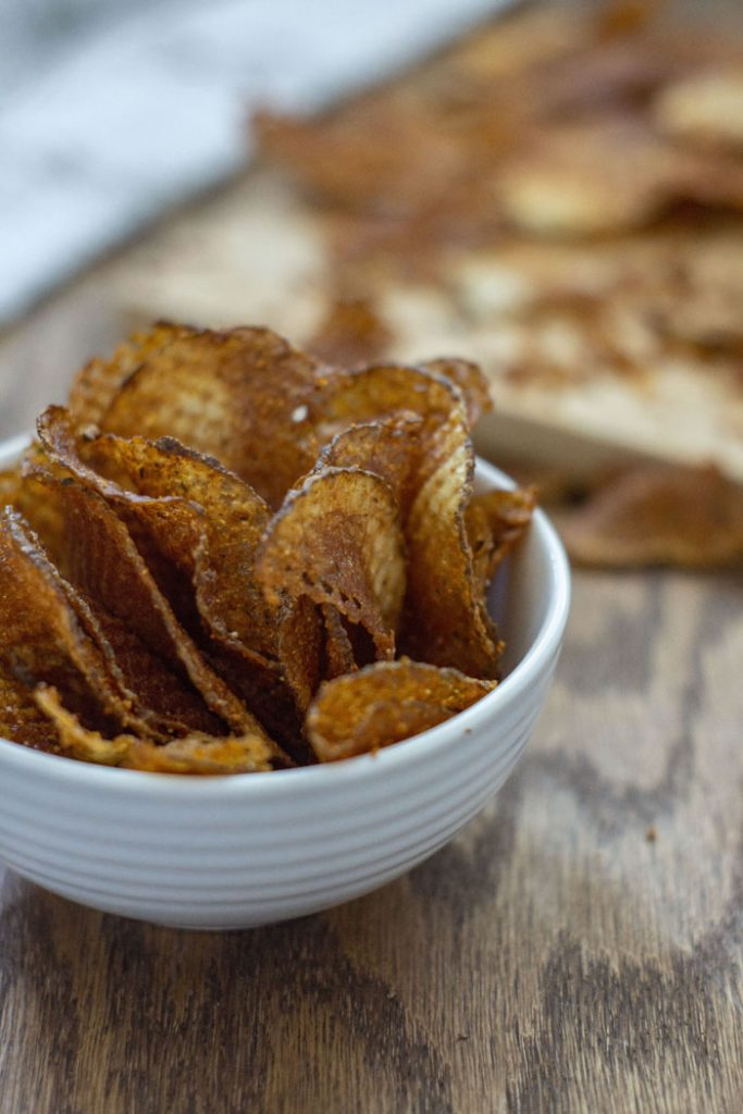 BBQ Waffle Chips in a small white bowl with crumbs in the background (vertical)