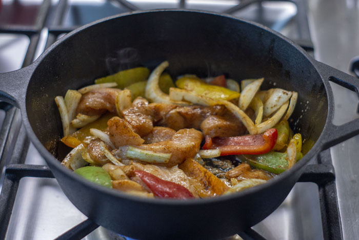Chicken fajita meat and veggies in a cast-iron pan on the stove before cooking