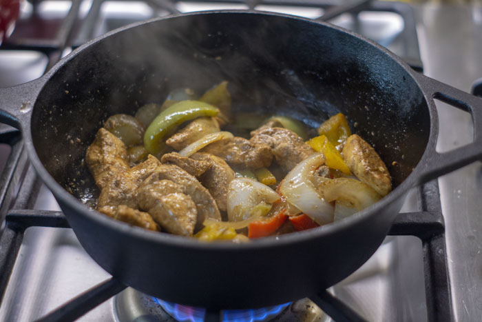 Chicken fajita meat and veggies in a cast-iron pan on the stovetop