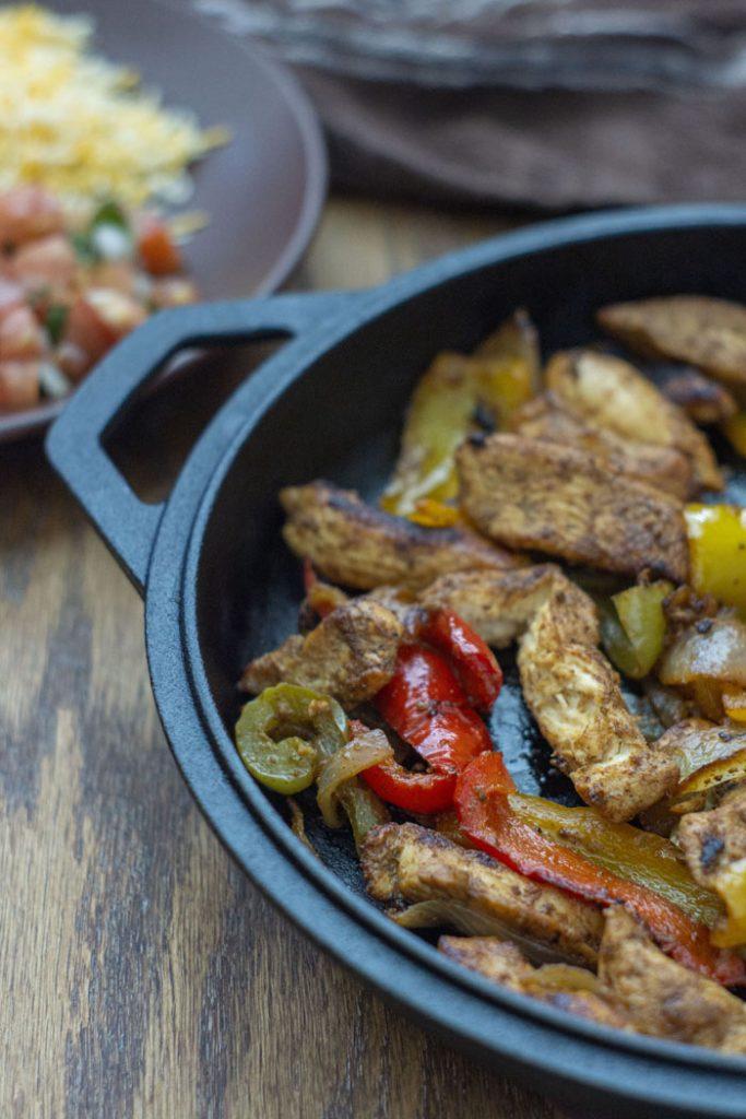 Chicken fajita meat and veggies in a cast-iron pan (vertical)