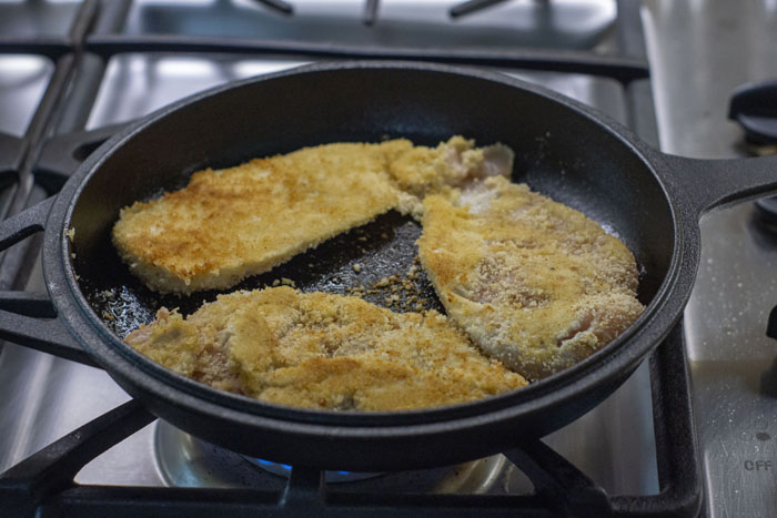 Breaded chicken in a shallow cast-iron pan on a gas stovetop
