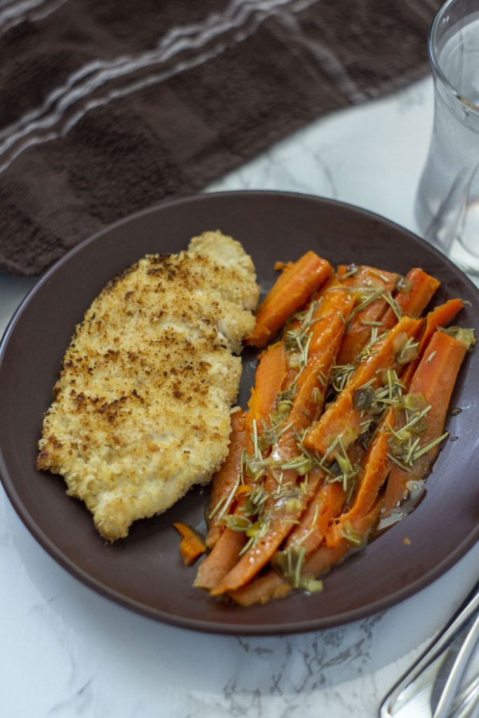Chicken and Carrots with Rosemary and Lemon Sauce on a brown plate (vertical)
