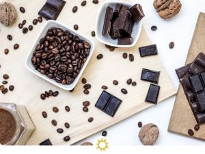 Overhead shot of coffee beans in a bowl, chocolate in another bowl, and pieces of chocolate and coffee beans on a wooden surface (with logo overlay)