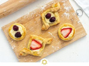 Breakfast pastries on a wooden cutting board next to a wooden rolling pin on a white background (with logo overlay)