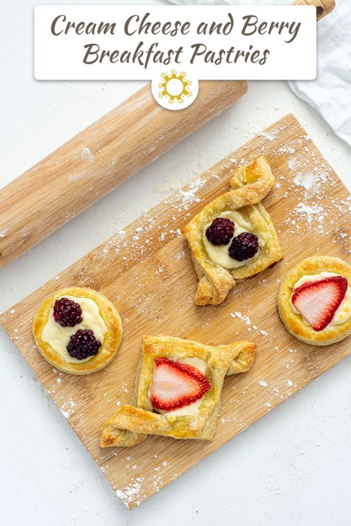 Breakfast pastries on a wooden cutting board next to a wooden rolling pin on a white background (with title overlay)