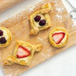 Breakfast pastries on a wooden cutting board next to a wooden rolling pin on a white background