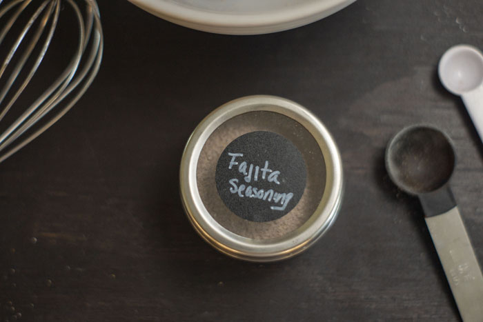 Fajita seasoning in a metal container with measuring spoons and wire whisk