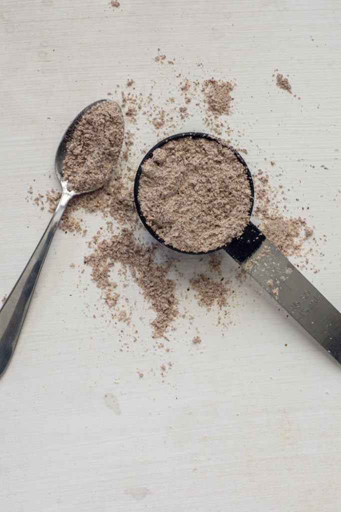 Measuring spoon and tea spoon with fajita seasoning on a white background with seasoning around it (vertical)