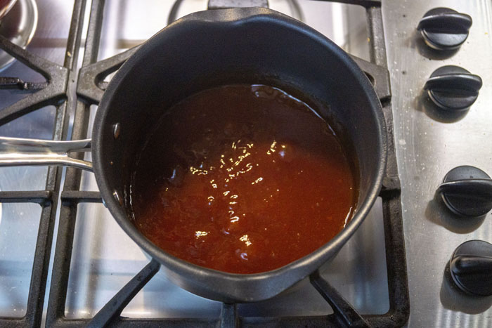 Sauce cooking in a sauce pot over a gas stove top