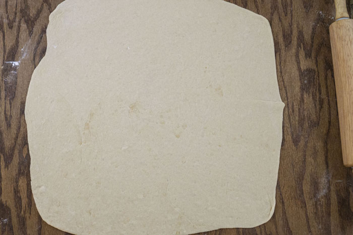 Dough rolled out on a wooden background next to a wooden rolling pin