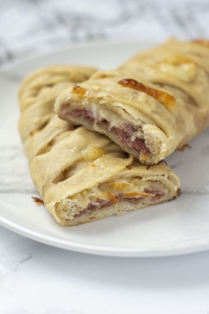 Salami and cheese hot pocket on a white and grey marbled plate (vertical)
