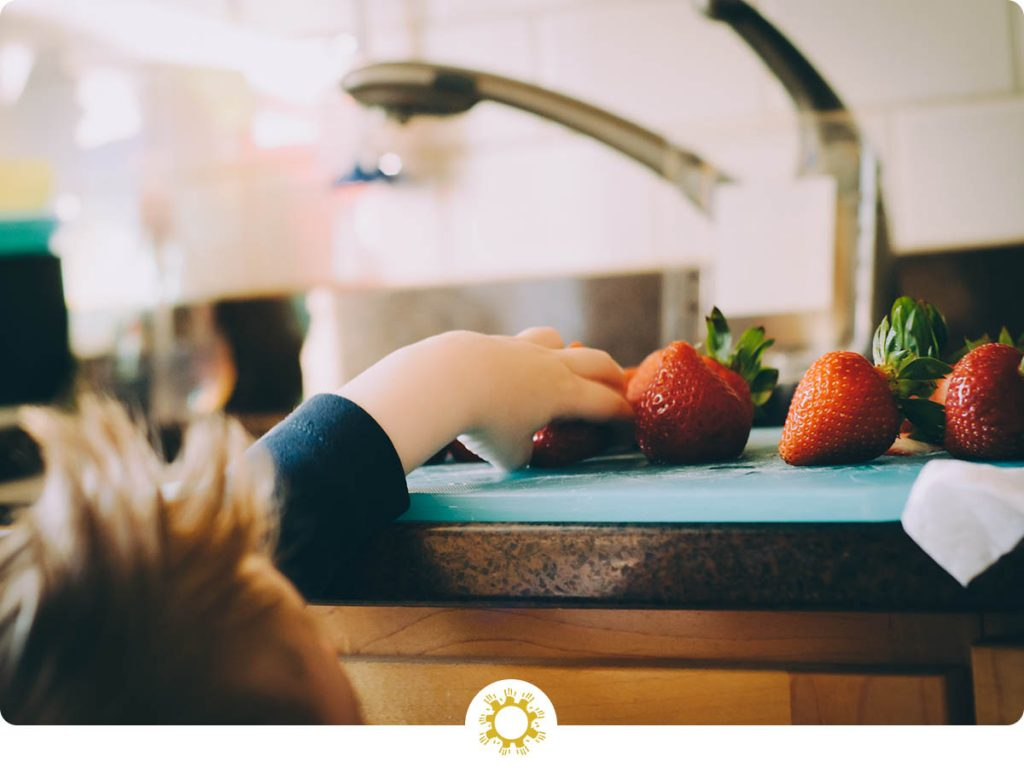 Boy grabbing strawberries off counter with logo overlay