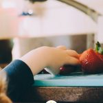 Young boy grabbing strawberries off a counter with Kids in the No Waste Kitchen title overlay