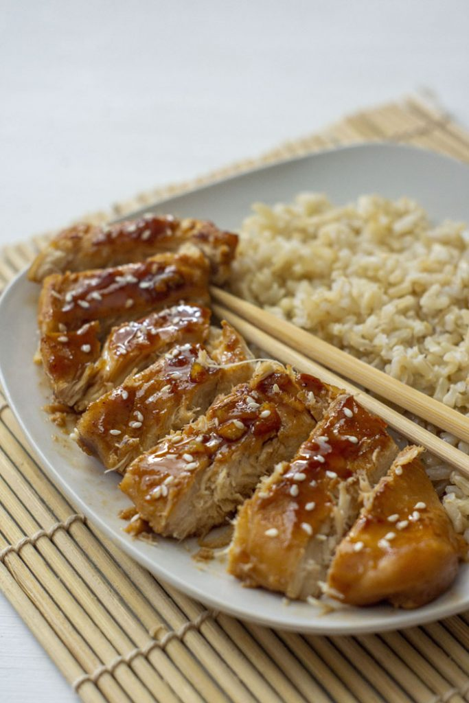 Orange chicken on a white plate with brown rice and chopsticks (vertical)