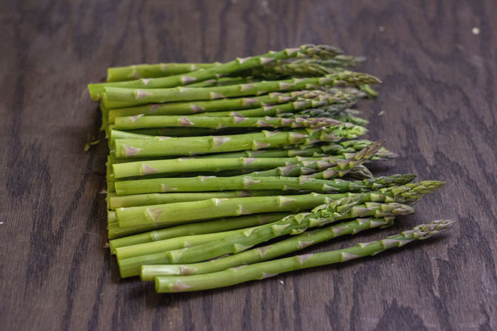 Raw asparagus on a wooden counter after the base has been cut off