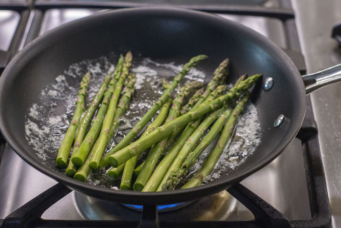 Asparagus in a pan with melted butter over a gas stovetop