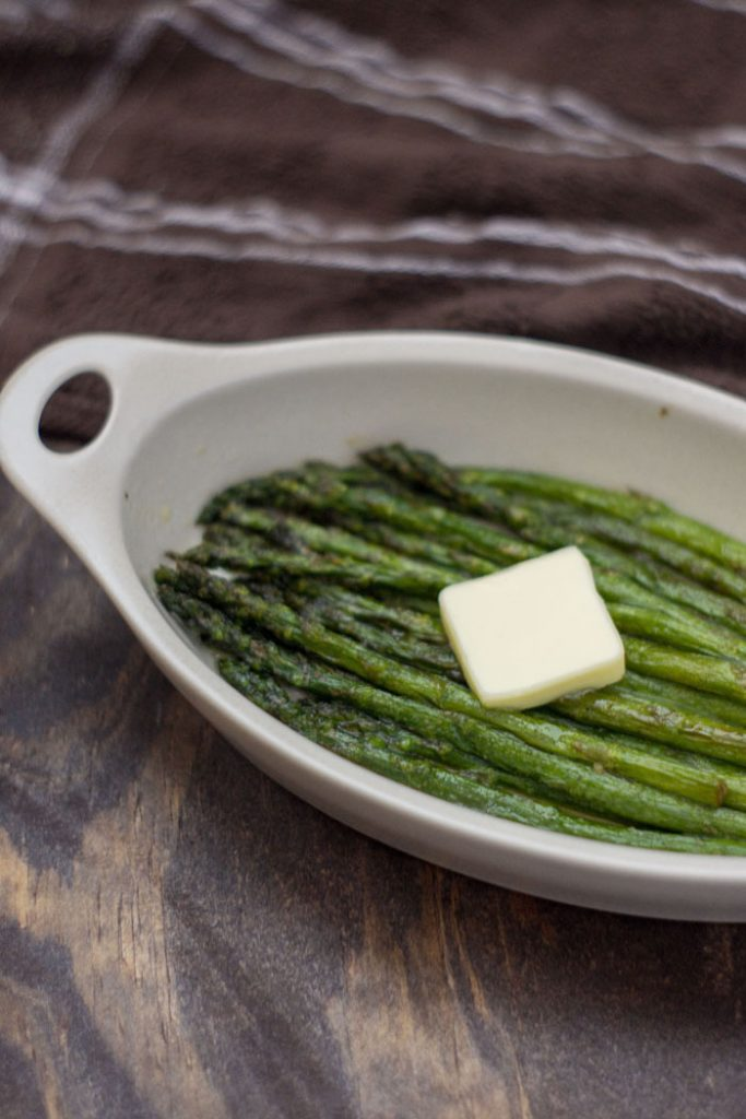 Roasted Asparagus in an oval bowl with a pat of butter on top (vertical)