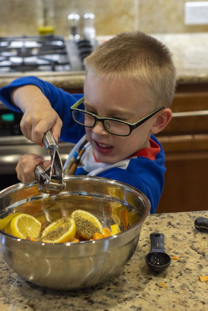 Young boy using a garlic press over a stainless steel mixing bowl