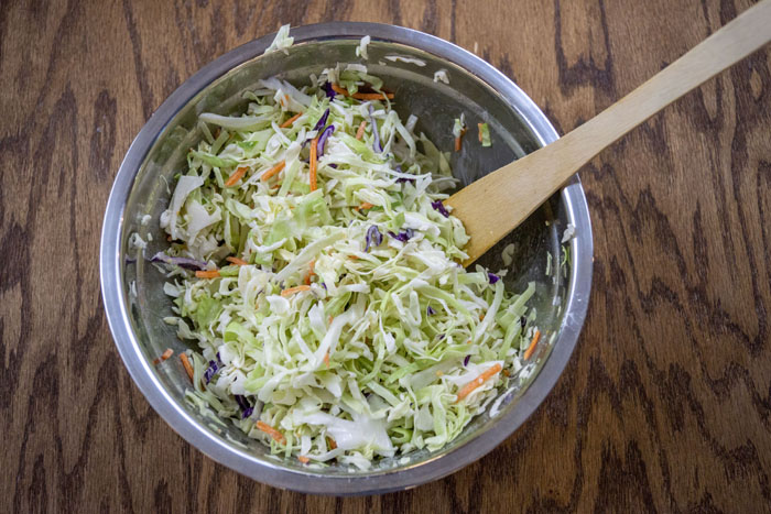 Coleslaw in a stainless steel bowl with a wooden backdrop